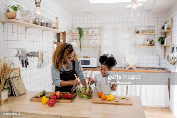 girl learning to prepare meal from mother - latin american and hispanic ethnicity stock pictures, royalty-free photos & images