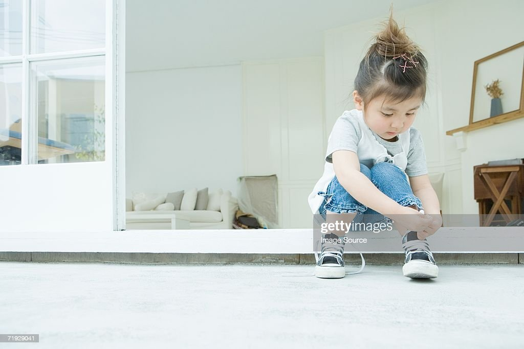 Girl learning to tie her shoelaces : Stock Photo