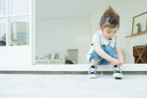 Girl learning to tie her shoelaces - gettyimageskorea