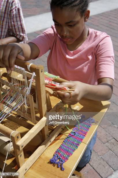 Girl learning to weave at the Kowtown Festival.