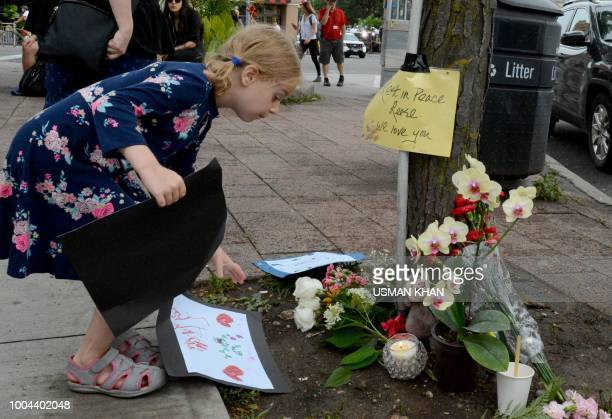 A girl leaves a drawing for the victims at the scene of last night shooting in Toronto Ontario on July 23 2018 Toronto police were seeking to...