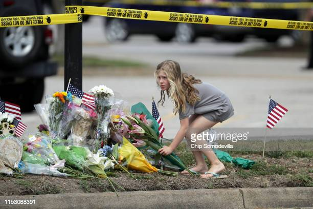 A girl leaves flowers at a makeshift memorial outside of the crime scene at the Virginia Beach Municipal Center June 01 2019 in Virginia Beach...