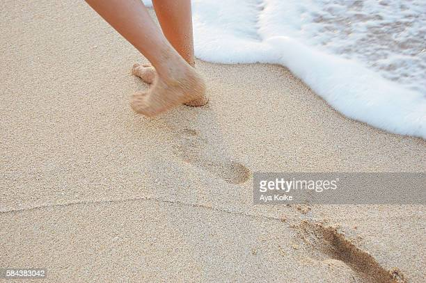 A girl leaving footprints in the sandy beach, Hawaii