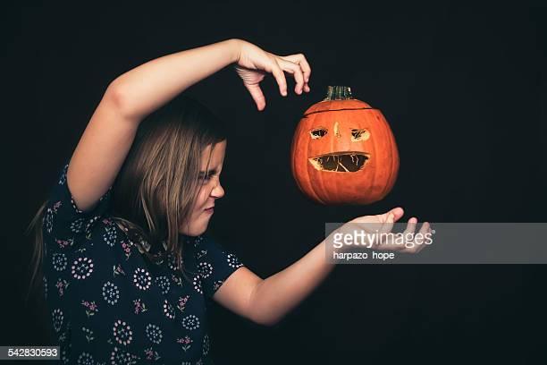 Girl levitating a jack-o'-lantern