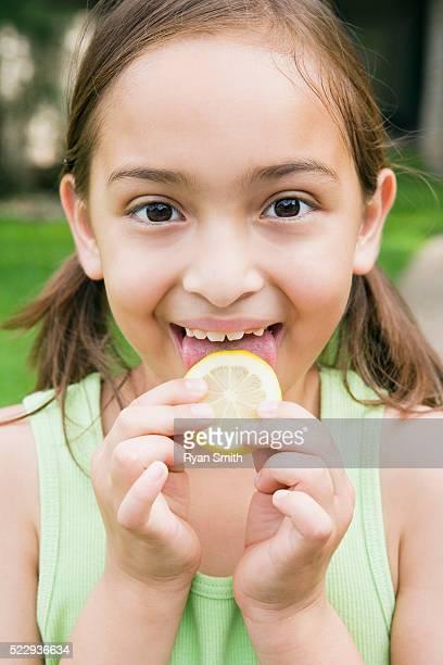 Girl licking a lemon slice