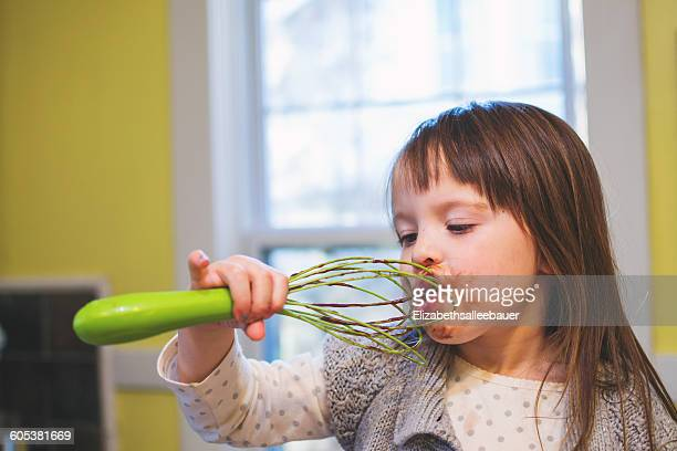 Girl licking chocolate cake mix  off a whisk