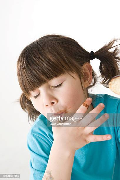 A girl licking chocolate off her thumb with relish