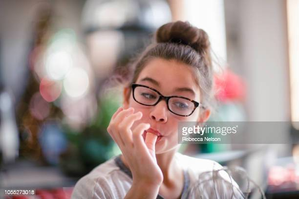 girl licking christmas cookie dough from fingers in kitchen - tasting stock pictures, royalty-free photos & images
