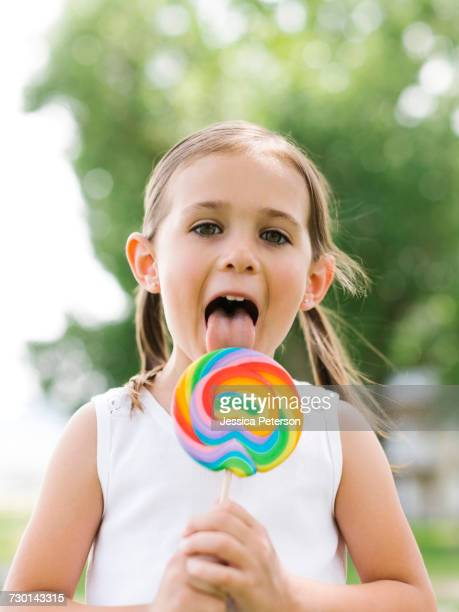 Girl (4-5) licking colorful lollipop