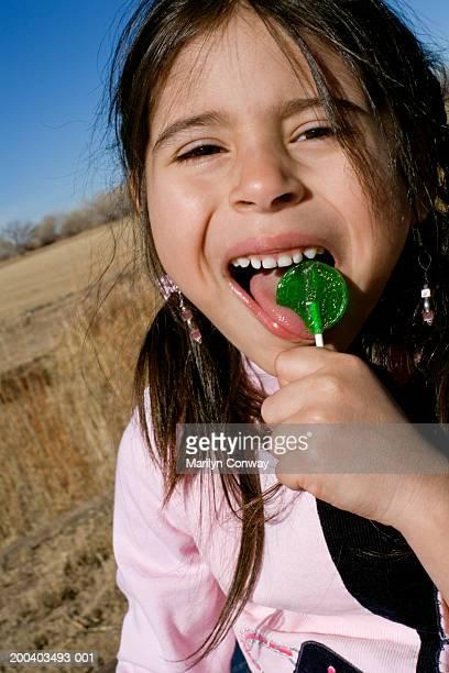 Girl (5-7) licking lollipop, close-up
