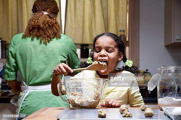 Girl (8-10) licking spoon from dough mixture