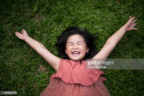 girl lie down on grass - toothy smile stock pictures, royalty-free photos & images