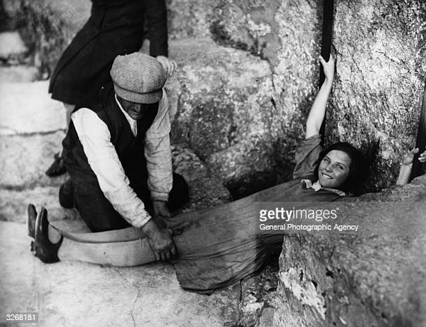 A girl lies flat on the ground in order to kiss the Blarney Stone in Blarney Castle Cork city