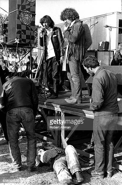 A girl lies in front of the stage as The Rolling Stones Tour Manager Sam Cutler tries to placate the crowd at The Altamont Speedway on December 6...