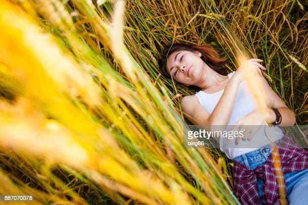 chica se encuentra en el campo entre las espigas de trigo