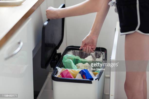 girl lifting a section from a recycling bin for emptying - garbage bin stock pictures, royalty-free photos & images