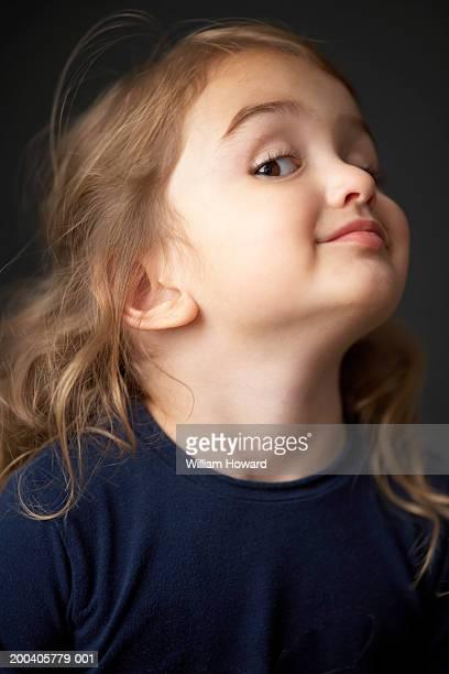 Girl (2-4) lifting chin up, looking down