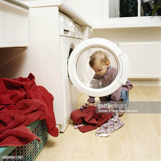 girl (2-4) lifting clothes by tumble dryer - tumble dryer stock pictures, royalty-free photos & images