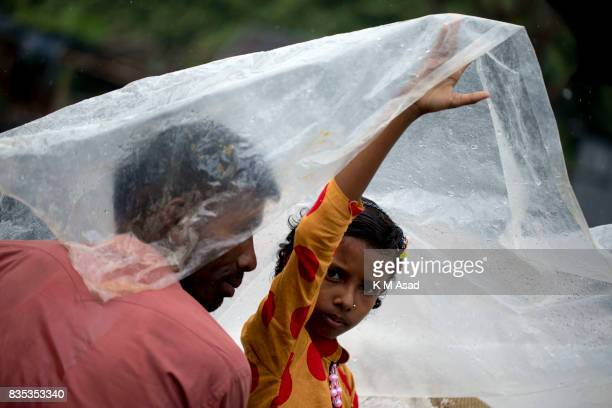 SARIAKANDHI BOGRA BANGLADESH A girl lifts a plastic sheet to protect herself from the rain at Shariakandi Bogra According to authorities floods...