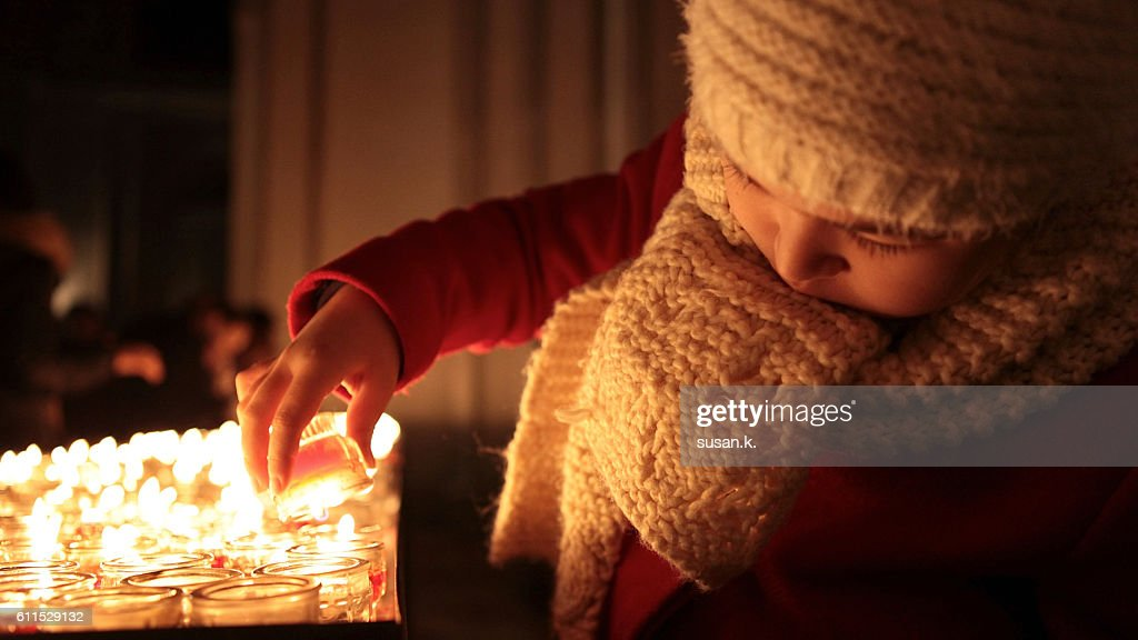 Girl lighting a candle in the church : Stock Photo