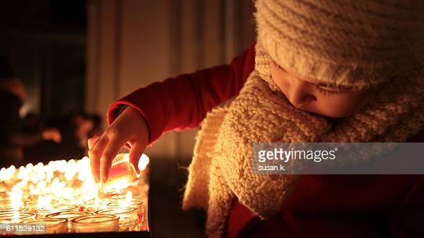 Girl lighting a candle in the church