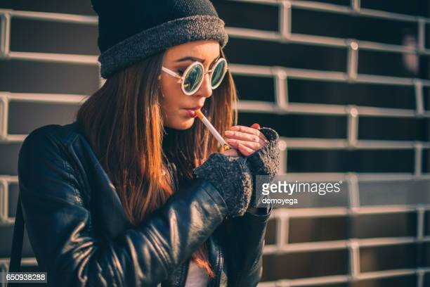 girl lighting a cigarette - beautiful women smoking cigarettes stock photos and pictures