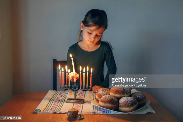 girl lighting candles on a menorah for traditional winter jewish hanukkah holiday at home. - sufganiyah stock pictures, royalty-free photos & images