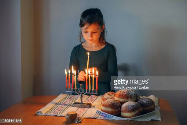 girl lighting candles on menorah for traditional winter jewish hanukkah holiday at home. - sufganiyah stock pictures, royalty-free photos & images