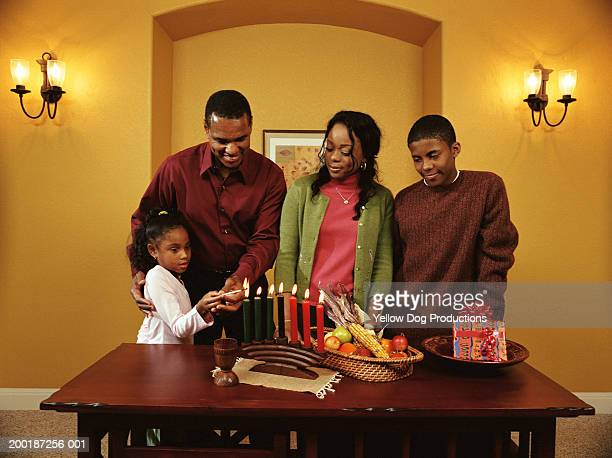 Girl (6-8) lighting Kwanzaa candles with family