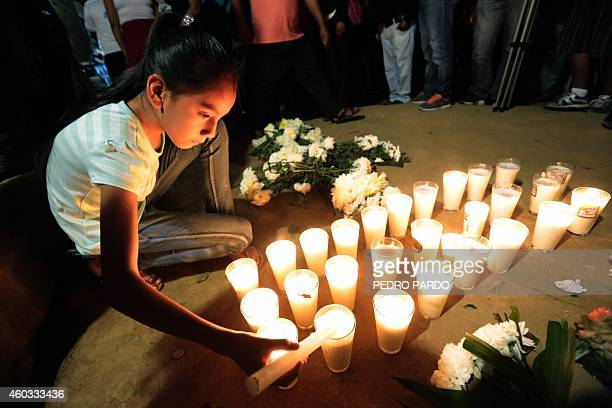 A girl lights a candle during the vigil of Alexander Mora one of the 43 missing students whose remains were found in a landfill in Cocula in the...
