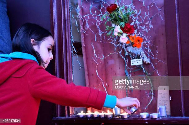 A girl lights a candle next to a placard reading Say no to obscurantism in front of a broken window of Le carillon restaurant one of the site of the...