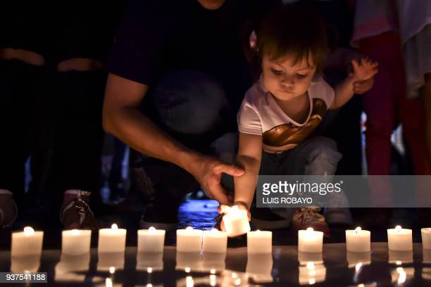 A girl lights candles and form 60 sign during the Earth Hour environment campaign in Cali Valle del Cauca department Colombia on March 24 2018 Earth...