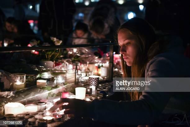 A girl lights candles as people gather on December 13 in memory of the victims of the attack near the Christmas market of Strasbourg in eastern...