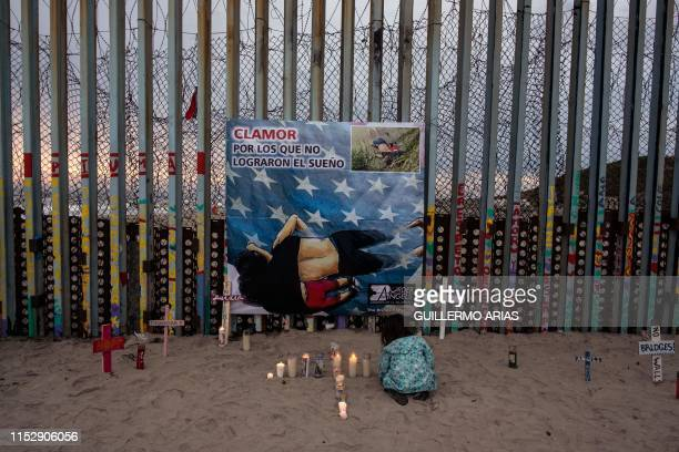 A girl lights candles next to a poster with a painting of Oscar Martinez and Valeria hung for an event called Clamor for those who didn't achieve the...