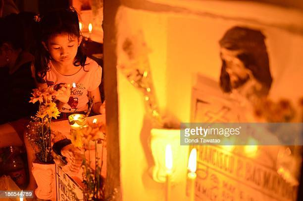 A girl lights candles on the crypt of a loved one at a public cemetery for All Saint's Day November 1 2013 in Marikina City Philippines As the...