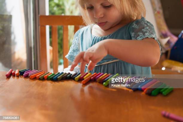 girl lining up crayons in a row - autismo foto e immagini stock