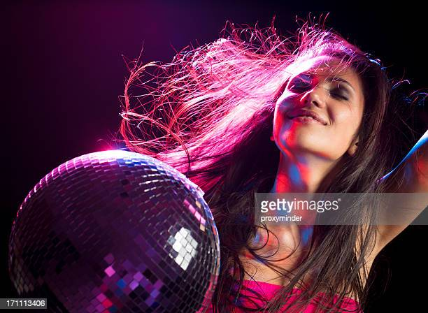 Girl listening music and dancing with disco ball