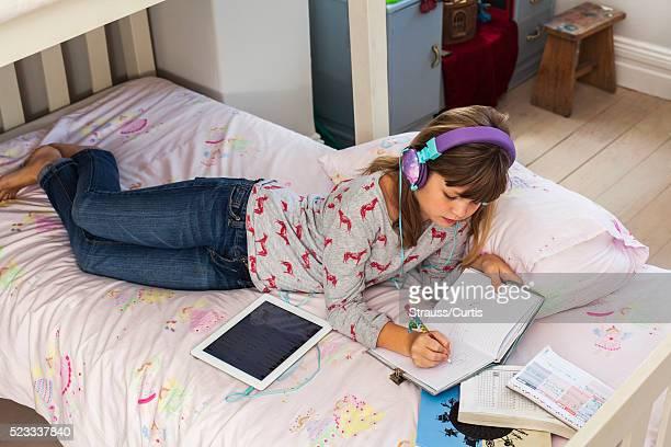 Girl (10-12) listening music and doing homework on bed