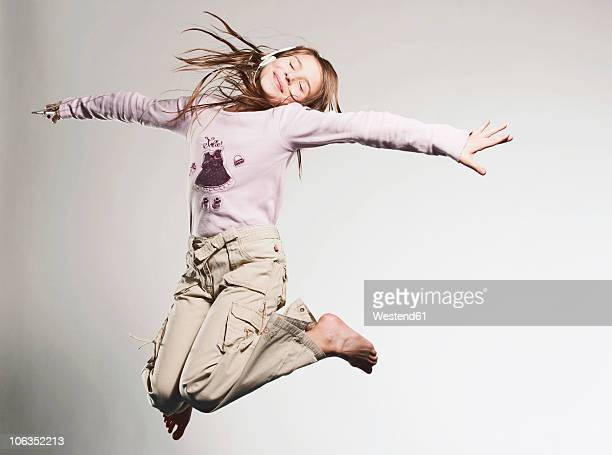Girl (10-11) listening music and jumping