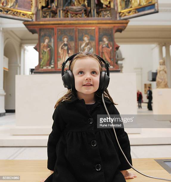 Girl listening to commentary on headphones in museum