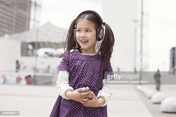 Girl listening to headphones and singing outdoors