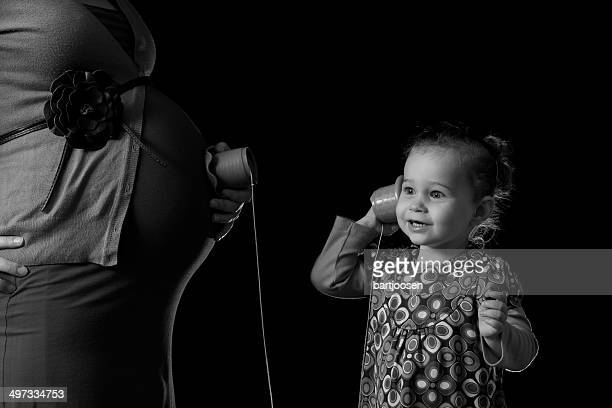 Girl listening to her pregnant mother's abdomen with a toy string phone