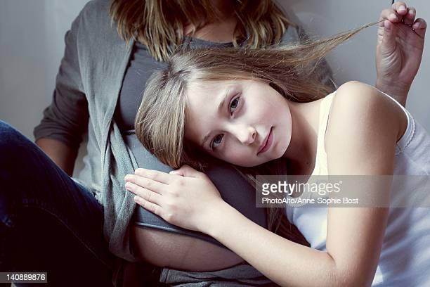 Girl listening to mother's abdomen