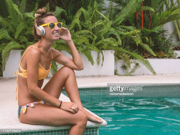 girl listening to music by the swimming pool - young woman wearing wireless headphones and relaxing on vacations in tropical  destination - tropical music stock photos and pictures