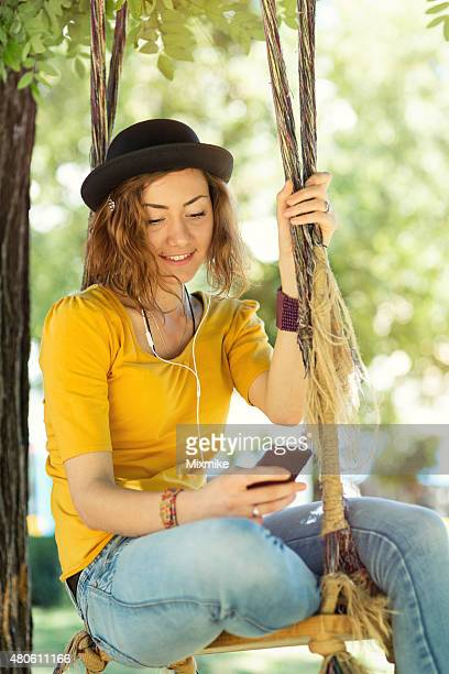 Girl listening to music on a swing