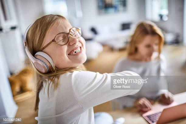 Girl listening to music on headphones with mother using laptop at home