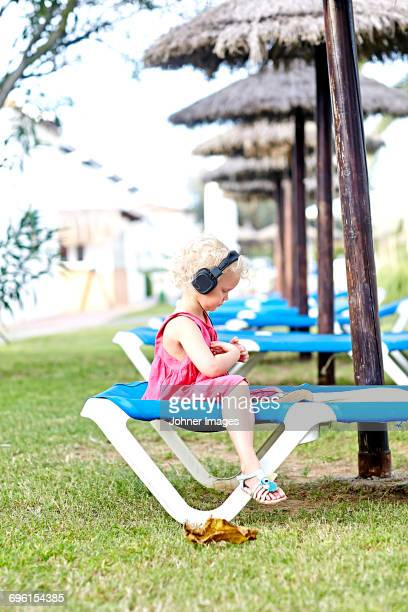Girl listening to music on lounge chair