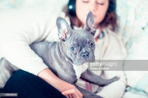 Girl listening to music on wireless headphones in her bedroom