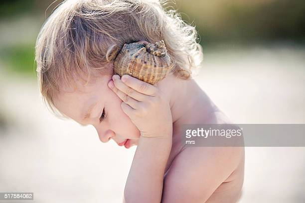 Girl listening to seashell on beach