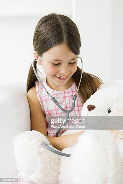 Girl listening to teddy's bear's heart with stethoscope
